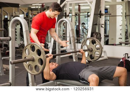 Young Man Spotting Each Other In A Gym