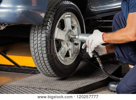 Technician Screwing Car Tire With Pneumatic Wrench