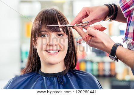Hairdresser cutting woman bangs hair in shop