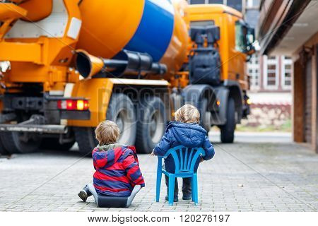 Two kid boys and concrete mixer near house
