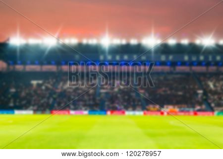 Blurry de-focused at stadium football twilight background.