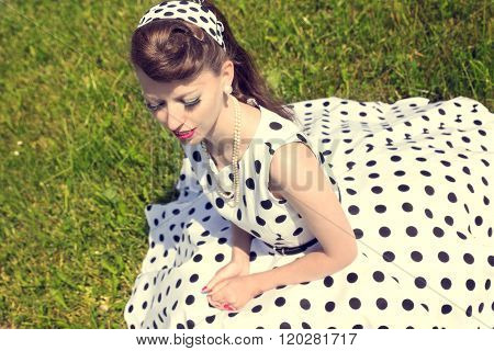 Woman With A Petticoat Dress, A Braid And A Suicide Roll Sitting On The Meadow