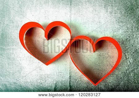 Two red paper hearts on Sackcloth background