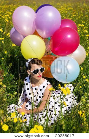 Beautiful Woman With A Rockabilly Style Dress Sitting On A Flowery Meadow With Colorful Balloons