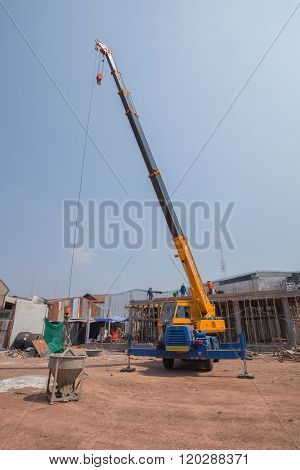 Crane Lifting Concrete Mixer Container At Construction Site