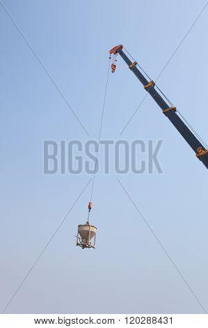 Crane Lifting Concrete Mixer Container Against Sky