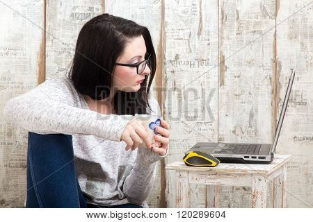 Student Girl Is Wearing Pair Of Glasses Is Studying On Laptop While Drinking From Her Mug.