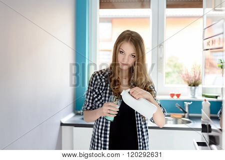 Blonde Woman Pouring A Milk In Kitchen