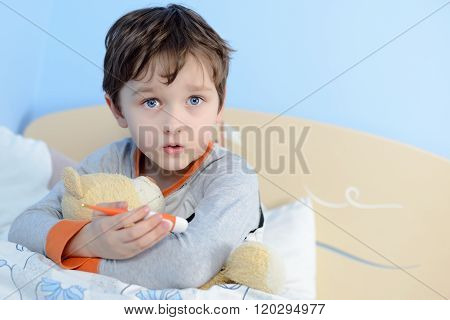 The little boy is sick. He lies in bed. Teddy Bear and thermometerer is in his hand.