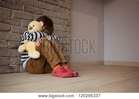 Sad Little Boy Sitting Against The Wall In Despair