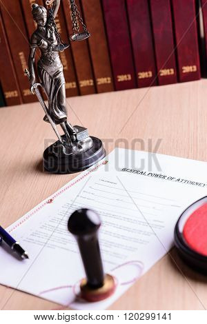 Notary public stamp on signed power of attorney. Pen and Themis with scales of justice in the background. poster