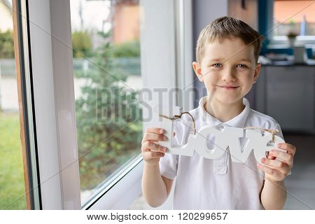 Happy little boy holding a wooden inscription with the word