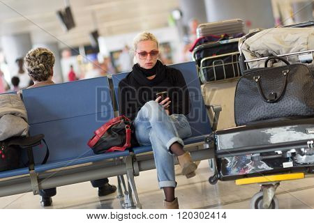 Female traveler using cell phone while waiting.
