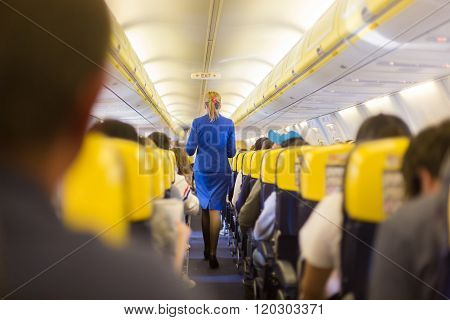 Stewardess and passengers on commercial airplane.
