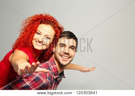Young couple in love having fun on grey background