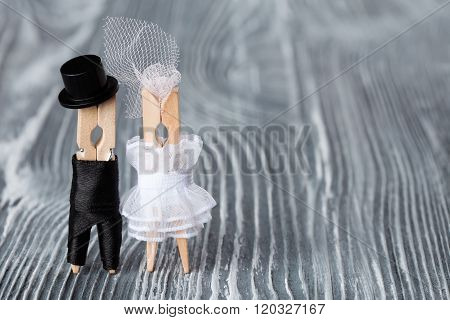 Wedding invitation card template. Clothespins Groom in black suit and bride white dress on gray wood