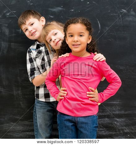 three different children stand one by one peeking out from behind each other with chalky blackboard on background