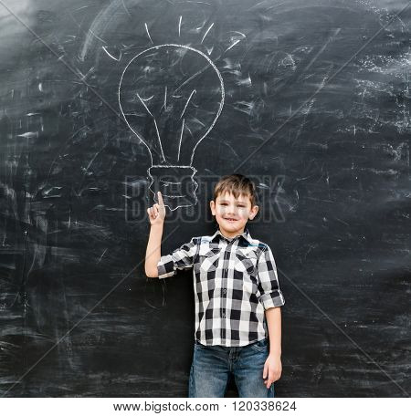 cute little boy with finger up having an idea with drawn lamp on chalky blackboard