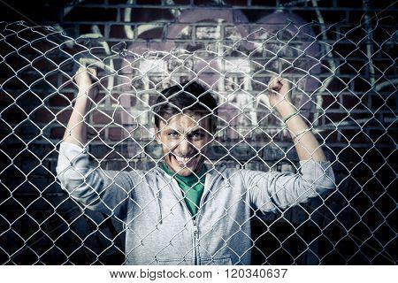 a young sad man behind bars close.