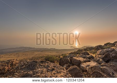 Sunset and ray path at the top of Antelope Island with rocks at the foreground
