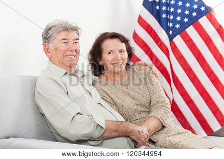 Cheerful senior couple seating in front of the American Flag