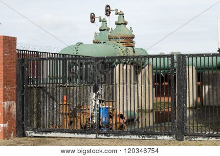 A gated site with green iron pipework raised on concrete pillars.