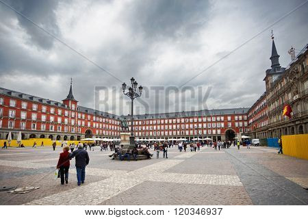 MADRID, SPAIN - OCTOBER 26, 2015 :People walk on the Plaza Mayor, in spite of the bad weather and the wind
