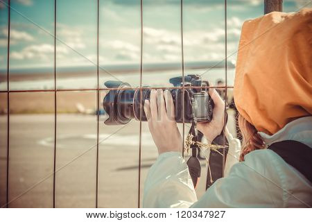 Spotter waiting for plane through the fence of Airport