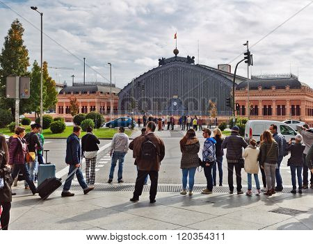 MADRID, SPAIN - OCTOBER 26, 2015 : People stand on pedestrian crossing on way to Atocha Old Train Station. Station is famous for its large roof from cast iron and glass, built between 1888 and 1892