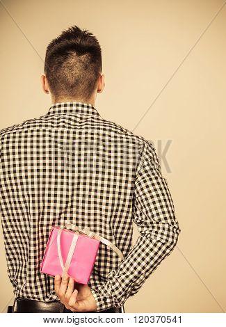 Man Hiding Gift Box Behind Back. Birthday Surprise