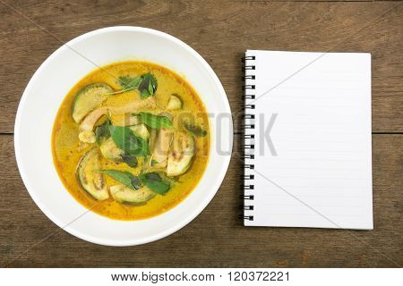 The delicious homemade Thai green curry with pork (Gang Keaw Wan) in white bowl and blank note book