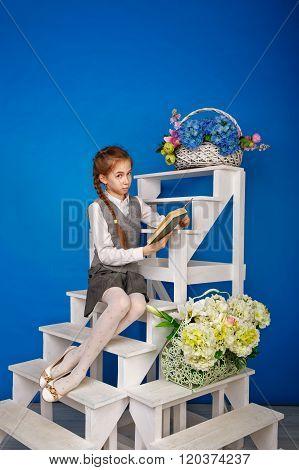 Teenage Girl In School Uniform Reading Book.