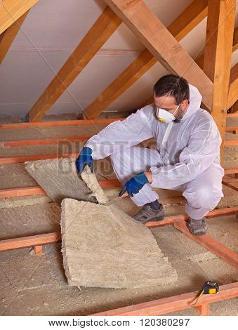 Worker Cutting Mineral Wool Panel To Install Thermal Insulation