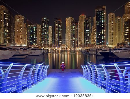 Dubai Marina At Night With Illuminated Blue Pier And Reflection Of Buildings On The Water