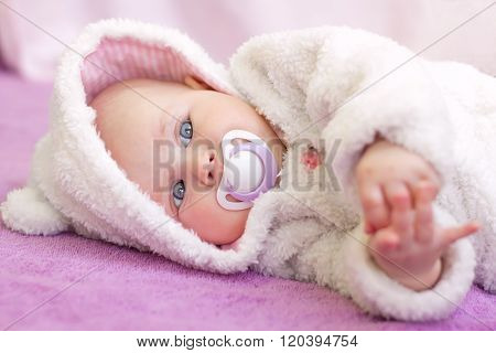 Cute baby girl with blue eyes in white fur lying with nipple.