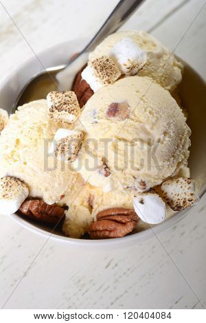 Bowl of delicious butter pecan ice cream with toasted pecans and marshmallows