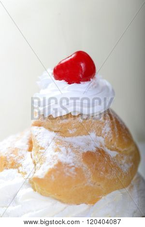 Delicious cream puff filled with whipped cream and topped with a cherry