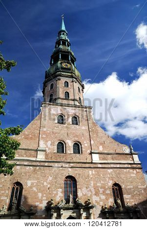 Saint Peters church tower in Riga, Latvia, against beautiful blue sky with clouds poster