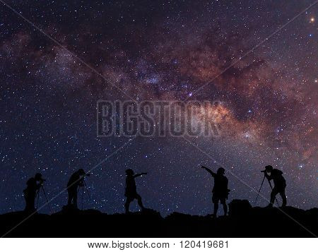 Star-catcher. A Person Is Standing Next To The Milky Way Galaxy Pointing On A Star