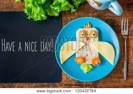 Funny sandwich owl for kids on plate, black chalkboard with Have a nice day greeting. healthy breakfast. Wooden table background