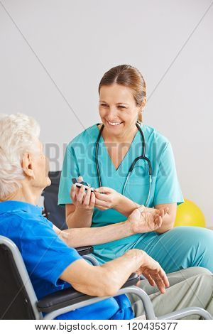 Geriatric caregiver doing blood sugar monitorin for old diabetes patient