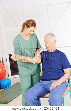 Old man sitting with shoulder pain in physical therapy