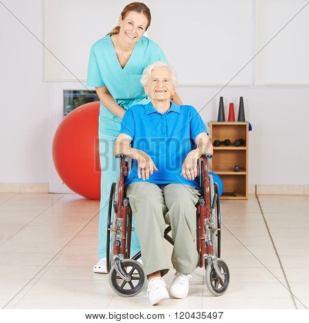 Geriatric nurse with old woman in wheelchair at physiotherapy