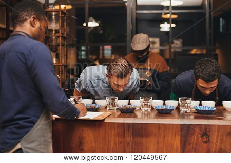 Barista training with rows of different coffees in roastery