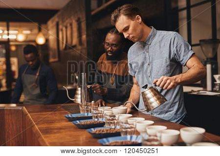 Baristas preparing a coffee tasting in modern roastery