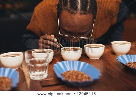 African man smelling the aroma of coffee at a tasting