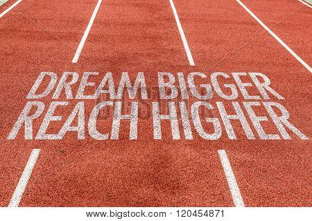 Dream Bigger Reach Higger written on running track