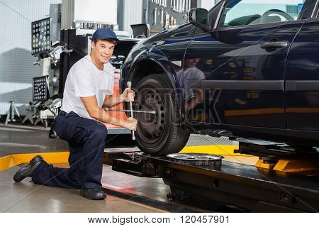Confident Mechanic Fixing Car Tire