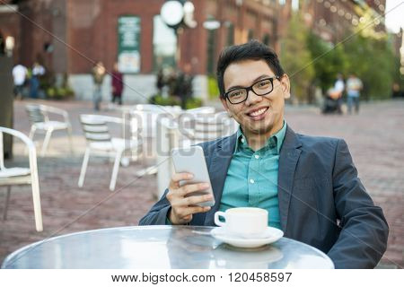 Young asian man in business casual attire sitting and smiling in relaxing outdoor cafe with cup of coffee and mobile phone