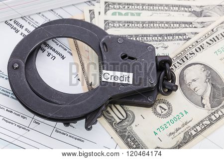 Handcuffs And Money With Sign – Credit On Tax Form Background